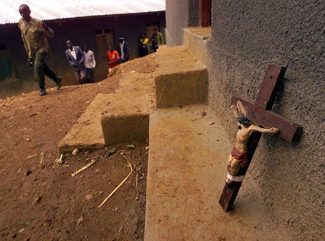 Mieszkańcy Kanungu i krzyż oparty o budynek sąsiadujący z kościołem, w którym spalono żywcem kilkaset osób.