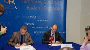 Przemysław Łągiewka i Narodowe Centrum Badań i Rozwoju podpisują umowę o sfinansowanie sporu prawnego z Uniwersytetem w Cambridge