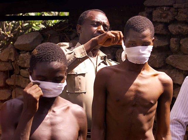 Ugandyjski policjant zakłada maski z gazy na twarze więźniów pracujących przy ekshumacji zwłok.