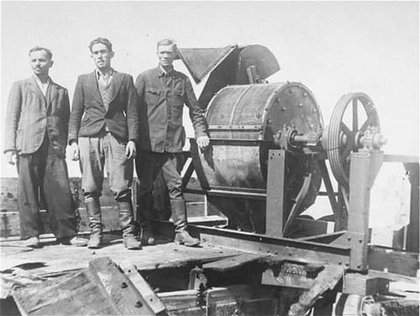 Członkowie jednostki Sonderkommando 1005 pozujący obok maszyny do kruszenia kości w niemieckim obozie koncentracyjnym Janowski.