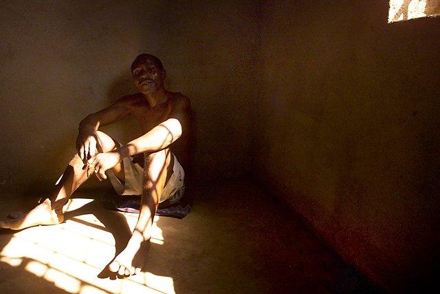 Wyczerpany więzień siedzi na podłodze domu, pod którego podłogą ukryto ponad 150 ciał zamordowanych członków sekty.